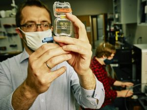 Stephan Warnat, left, and doctoral student Michael Neubauer, work on 3D-printed microfluidics chips with embedded sensors in their lab. (MSU Photo by Adrian Sanchez-Gonzalez)