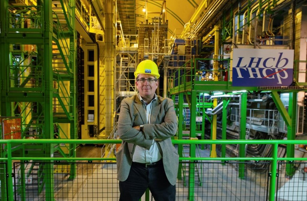 CERN scientist Guy Wilkinson stands in front of the LHCb detector. Image - CERN